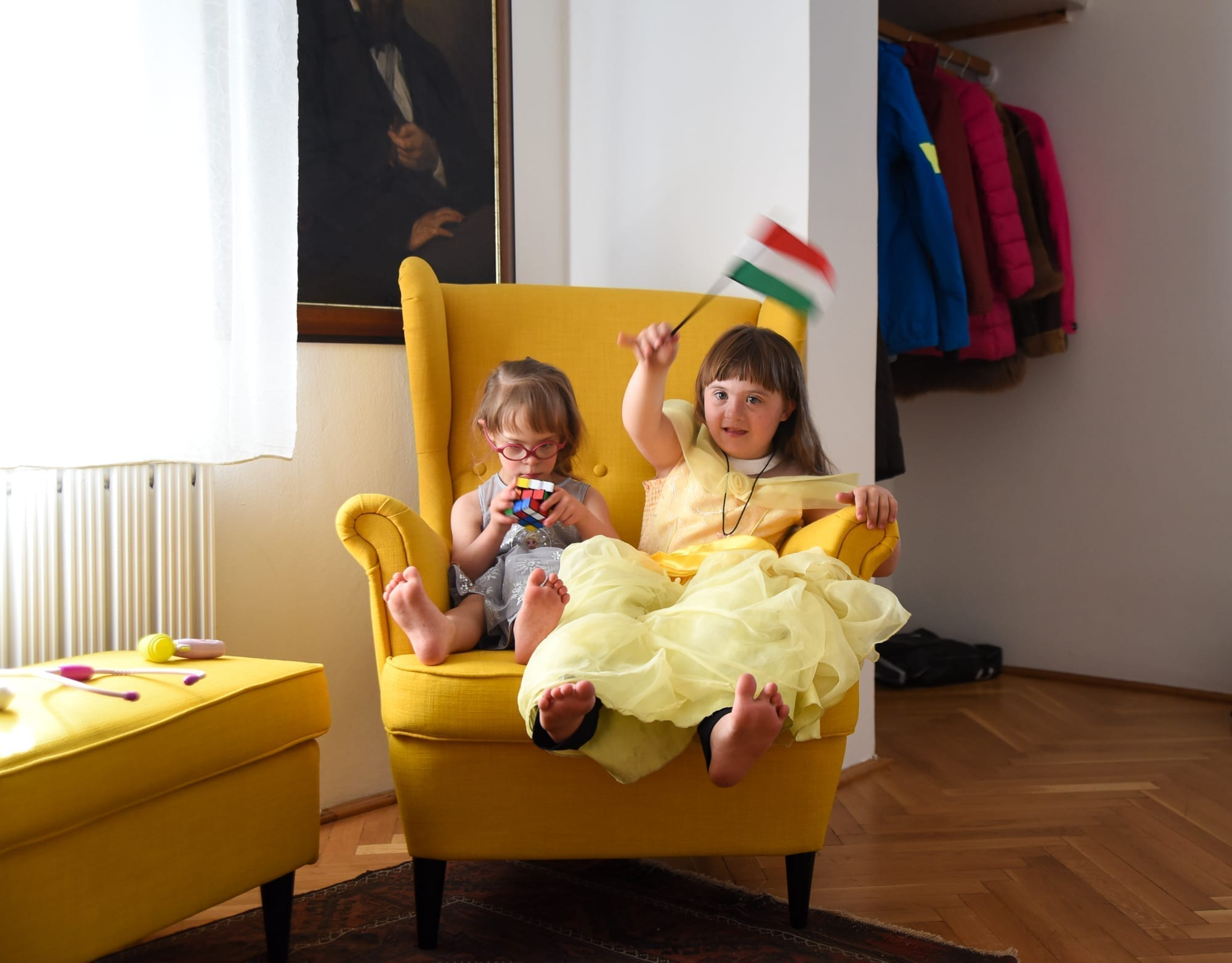 two girls sit on a chair and play with a rubix cube one is waving a hungarian flag