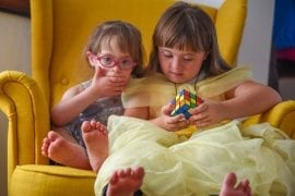 two girls sit on a chair and play with a rubix cube