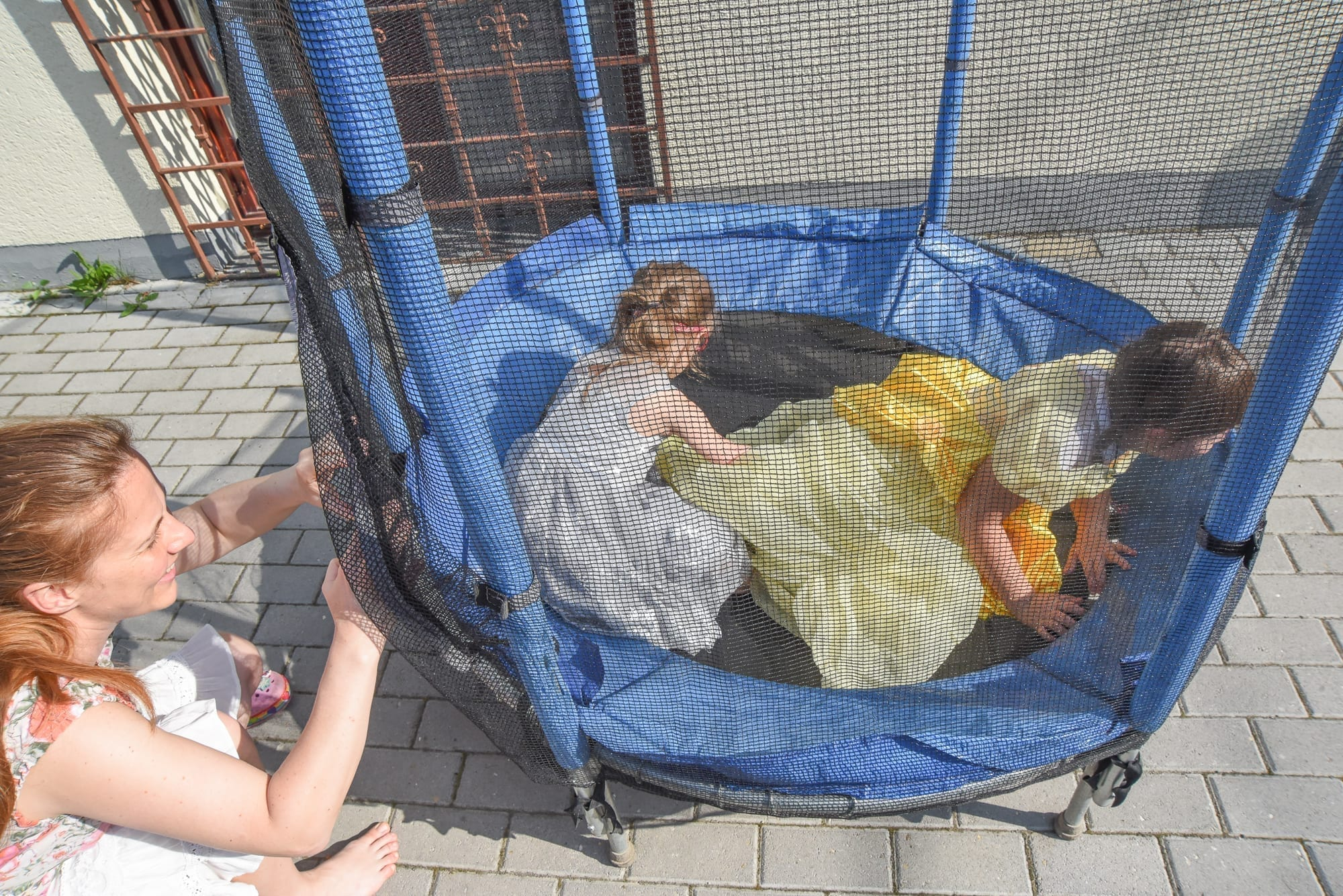 two little girls playing on a trampoline with a woman by them