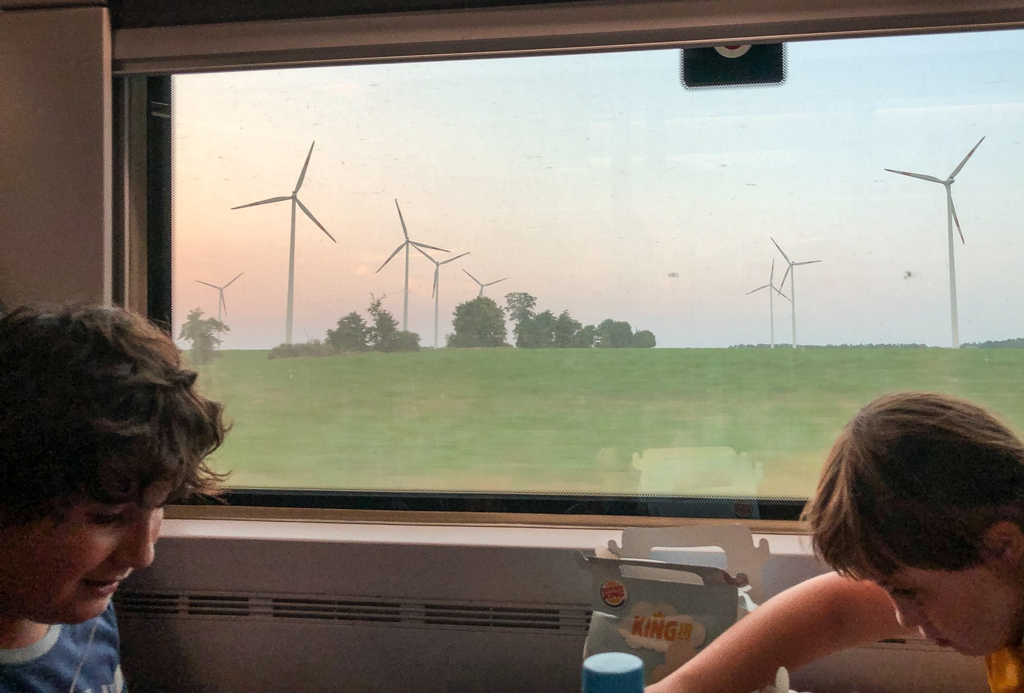 on the train in europe, image of two children by the window with windmills outside