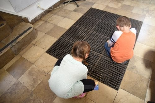 kids looking at money in a grate in syngoguge