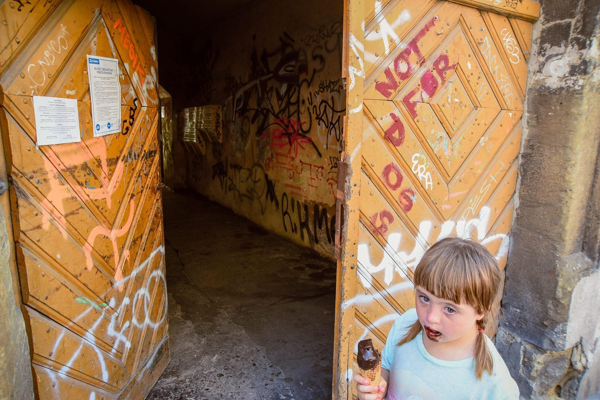 child with icecream on her face in front of open door with graffiti