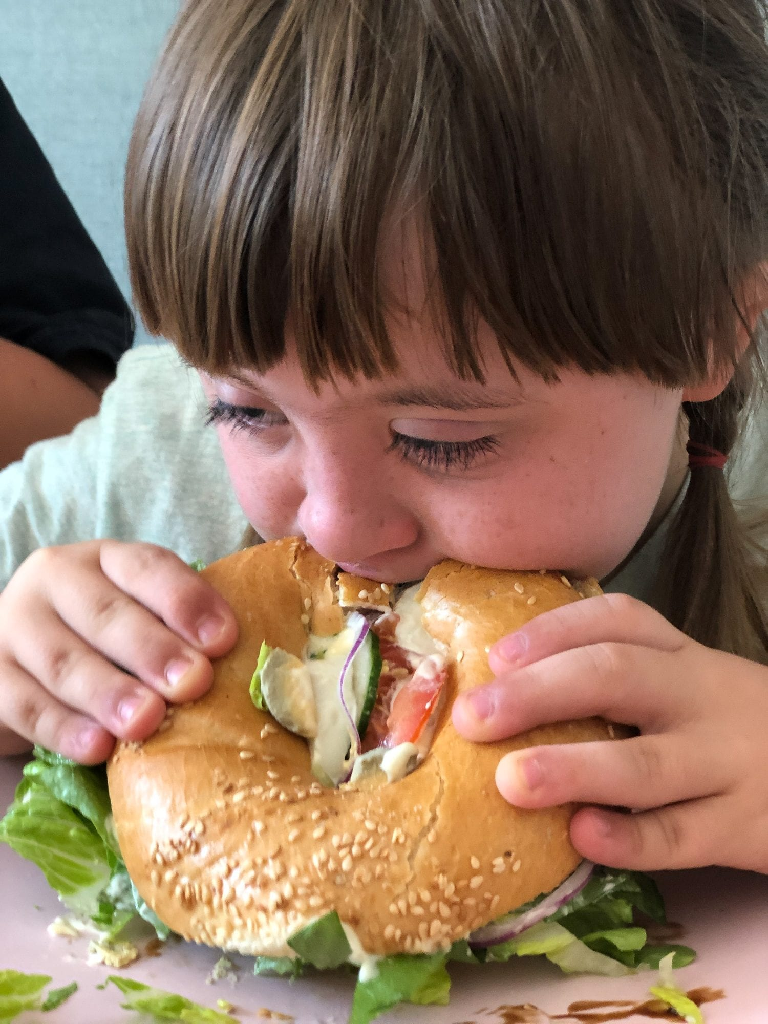 little girl biting into huge bagel sandwhich in krakow