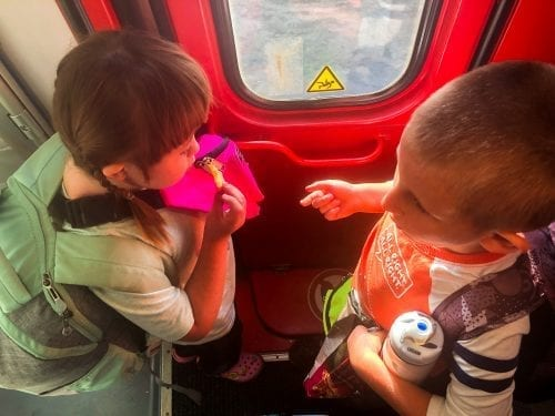 two children wait by train door in krakow