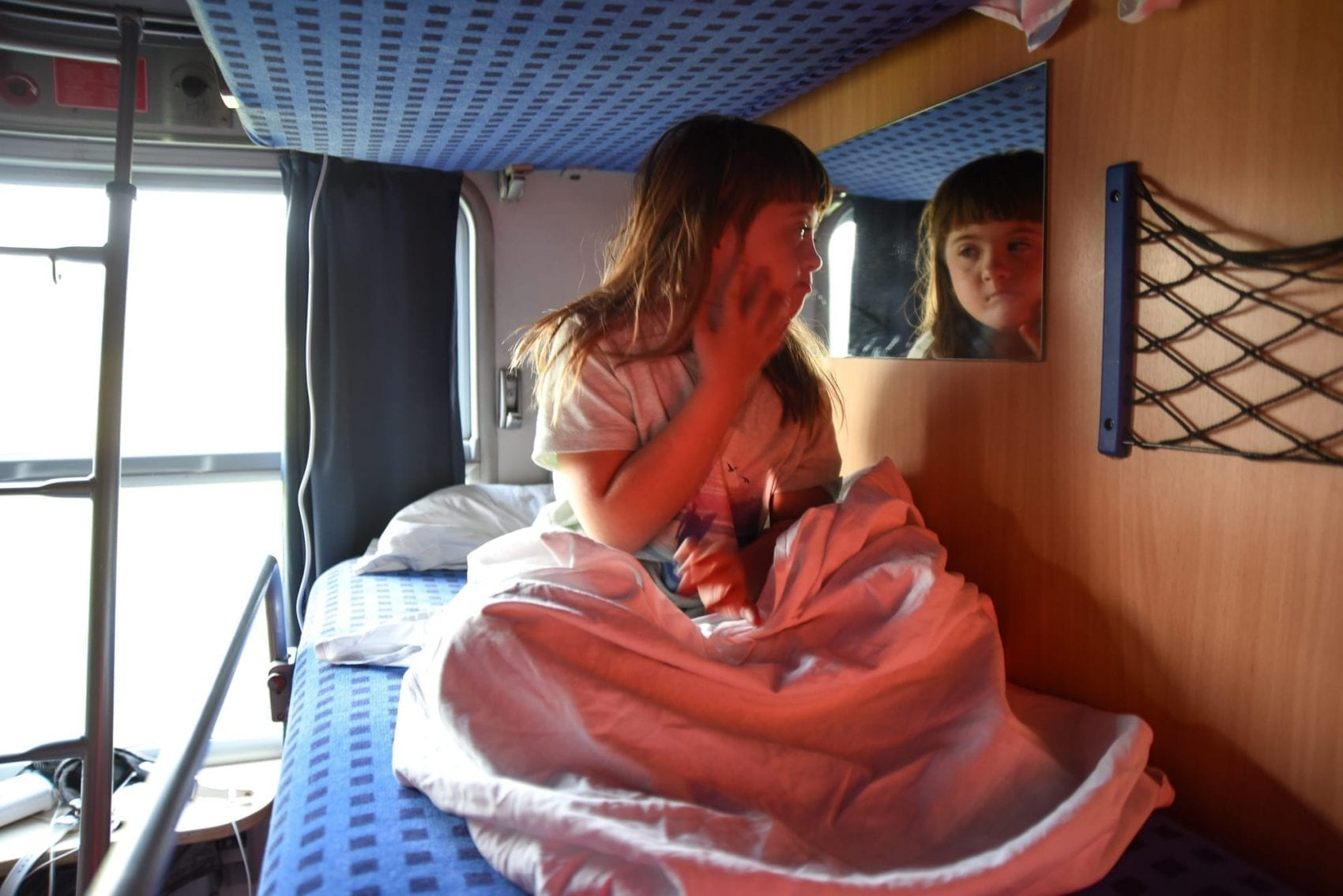 night train from budapest to krakow: a little girl looks in the mirror on her bunk at herself