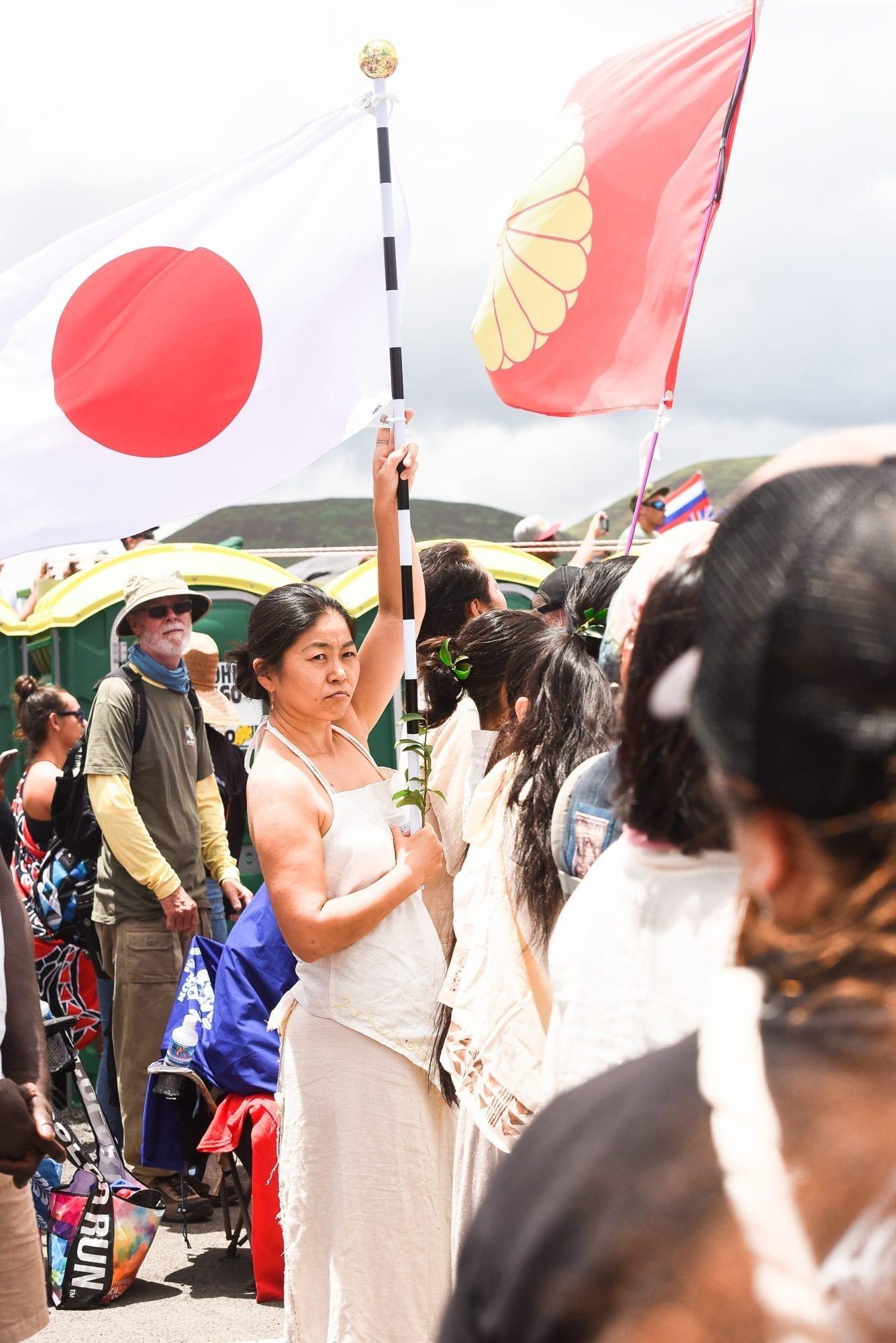 Japanese woman holding flag at Mauna Kea
