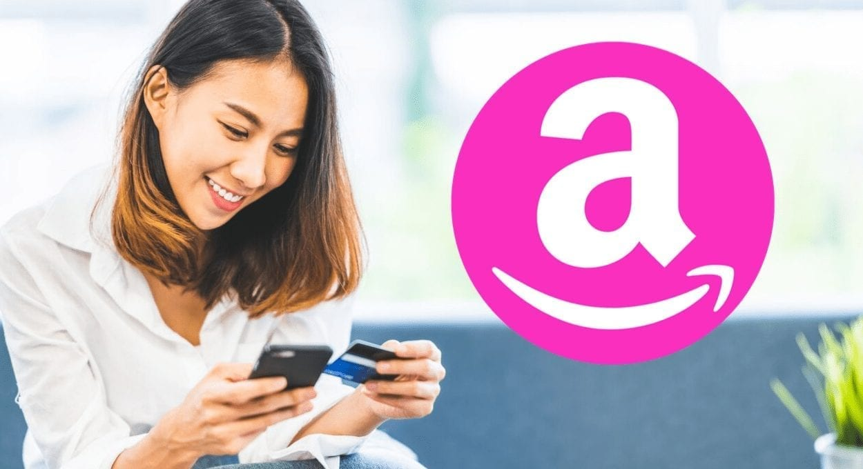 How to Get Amazon with EBT or Medicaid Card - or as a student! Image description: woman who appears asian is looking at her phone while holding a credit card. she is smiling. an amazon logo is in a pink circle to her right