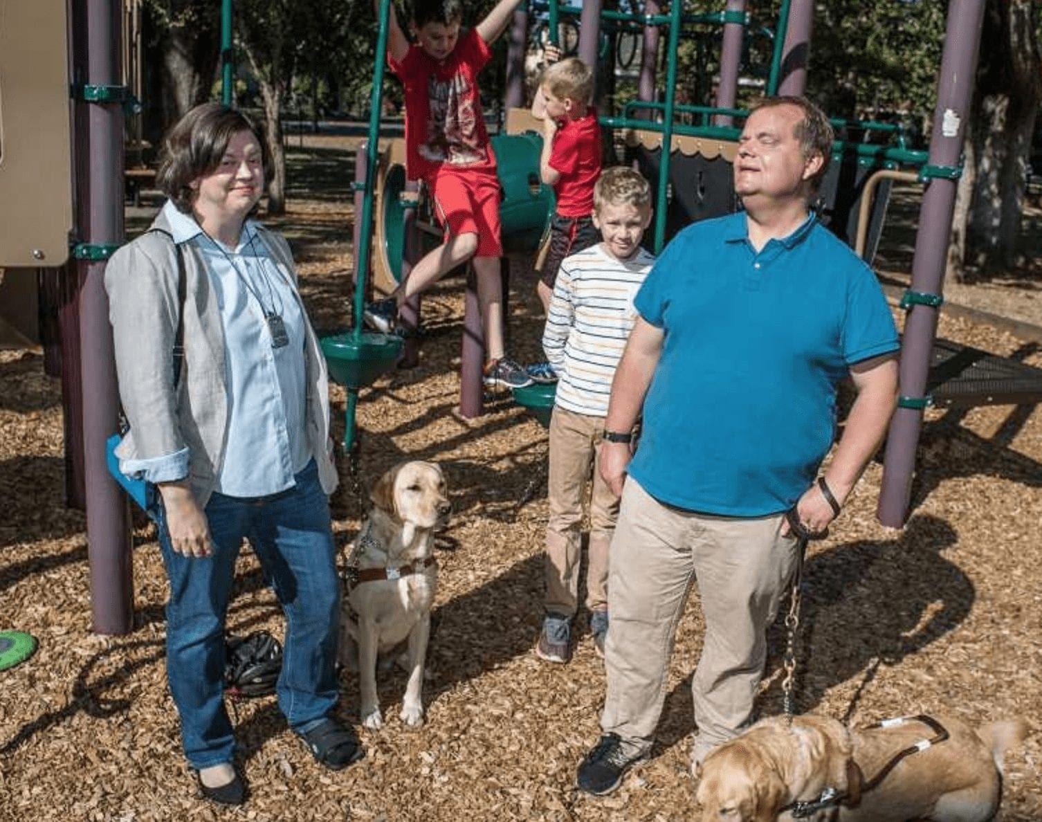 Lisa, her husband and guide dogs stand in front of a playground structure. In the background, their three sons play on the structure and look on in the background.