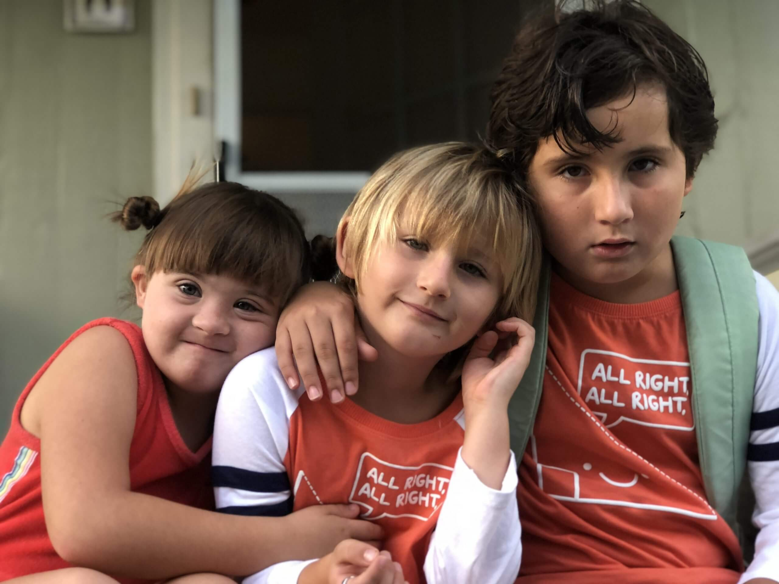 three children sit in front of a green house; they are all wearing orange shirts