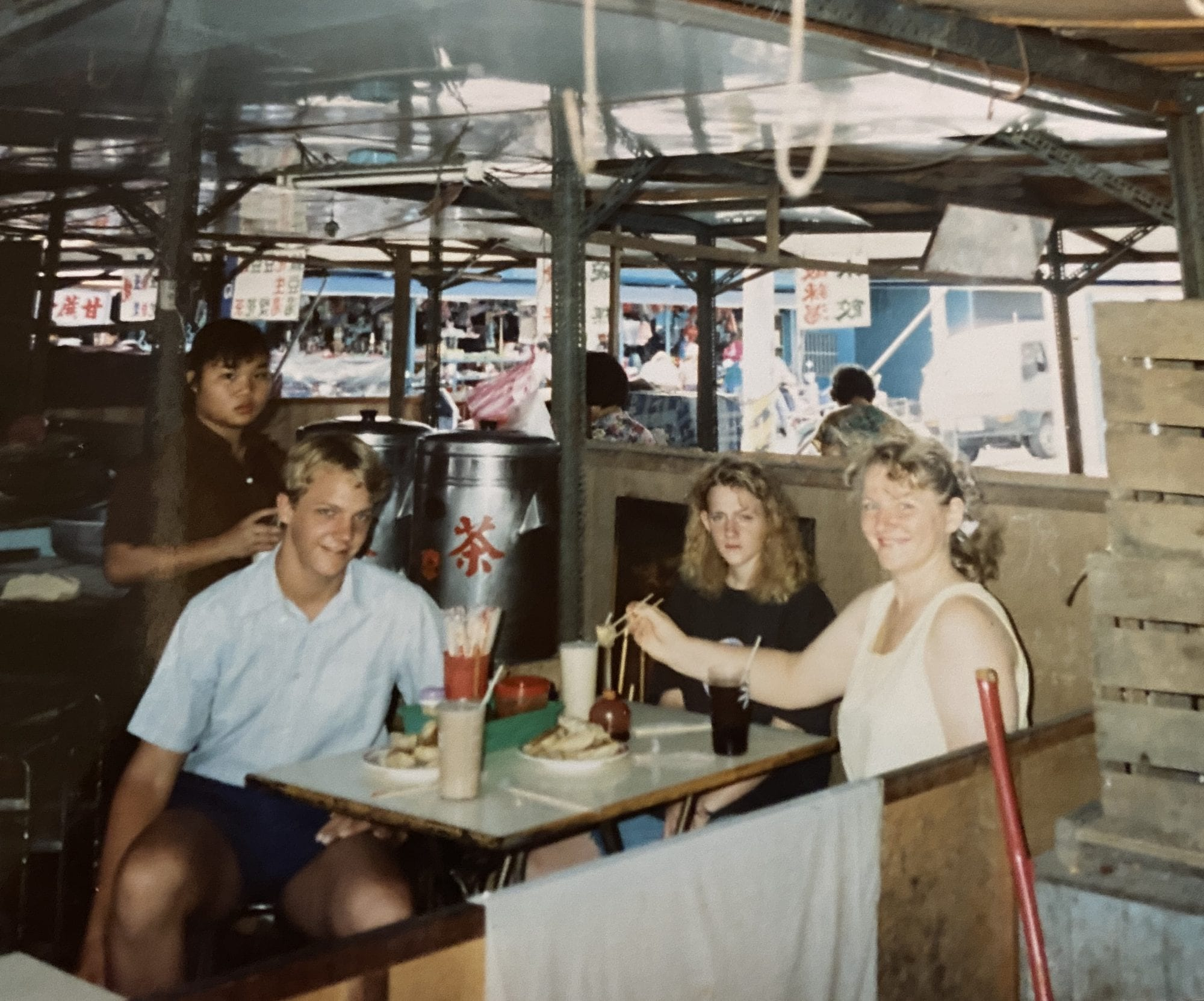 a young man with a white shirt is smiling, a girl with a black shirt looks like she is scowling, and a woman with a light shirt on is smiling brightly. there are plates of dumplings in front of them, and glasses of soybean milk. a woman in the back by the tea machine is looking on. 1990