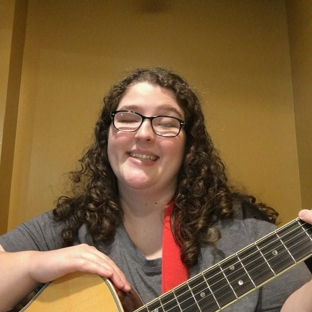 image of woman with dark brown, very curly shoulder-length hair and white skin, holding a guitar. she is wearing glasses, smiling, with a dimple. Her hand rests on the top of her guitar