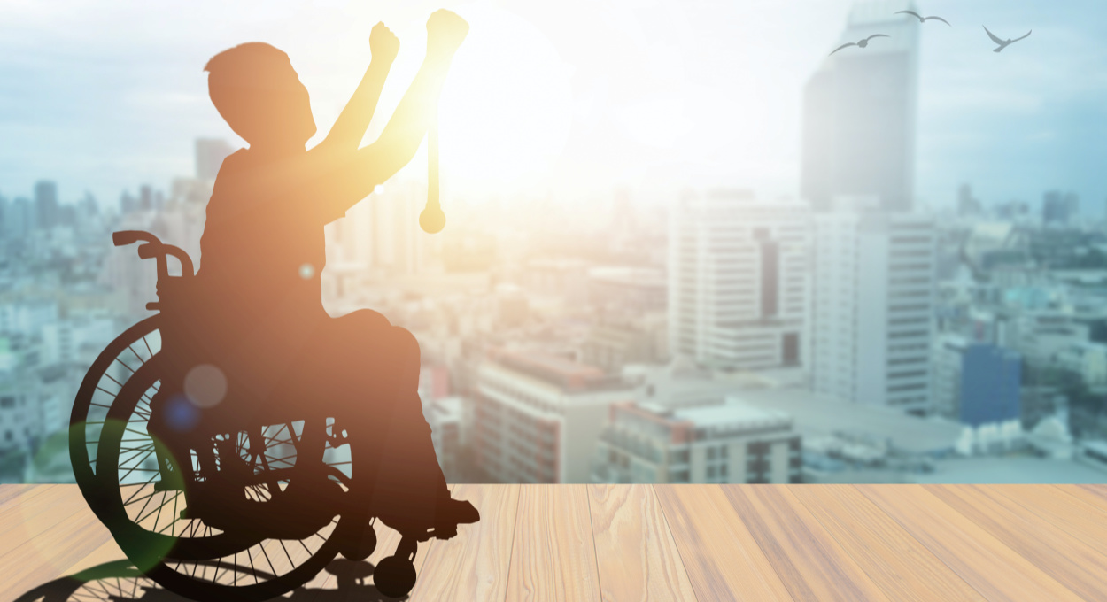 Nothing About Us Without Us - Disability and Global Expansion. ID: an individual sits in a wheelchair with arms upraised in victory. The person is in shadow, but overlooking the cityscape that is bathed in light
