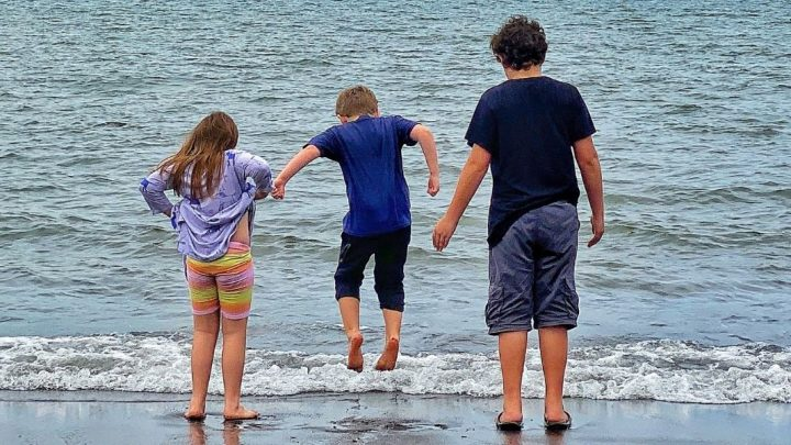 three children in front of the ocean, one child (in the middle) is jumping
