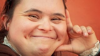 The Four F's of Disability Employment: image of a woman with Down syndrome, dark brown hair, and dimples, smiling as she holds her face up with her hand. The background wall is dark orange.