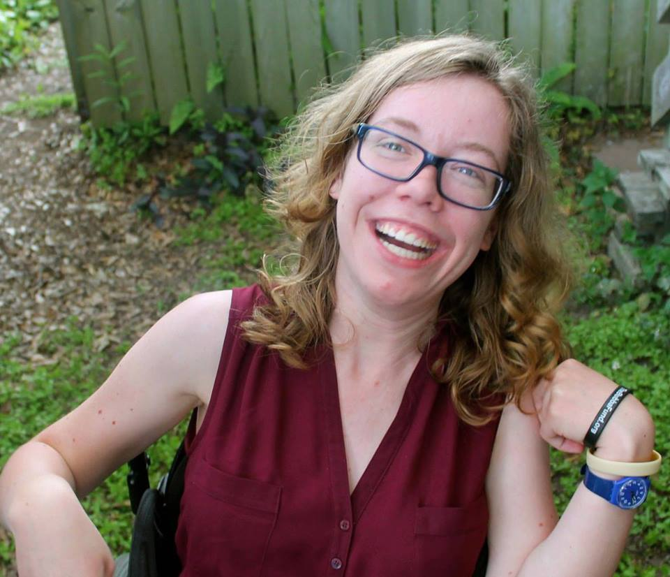 [Kathleen, a white woman seated in a wheelchair, is smiling with one arm on her armrest and the other bent upward with her fist touching her shoulder. She has blonde curly hair just past her shoulder and blue eyeglasses. She is wearing a maroon dress with buttons on the chest]