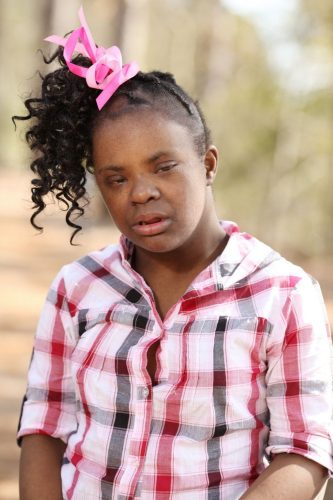 young girl with dark skin and pink check shirt and her hair up in a high ponytail looks to the side. she has down syndrome and seems to be in pain