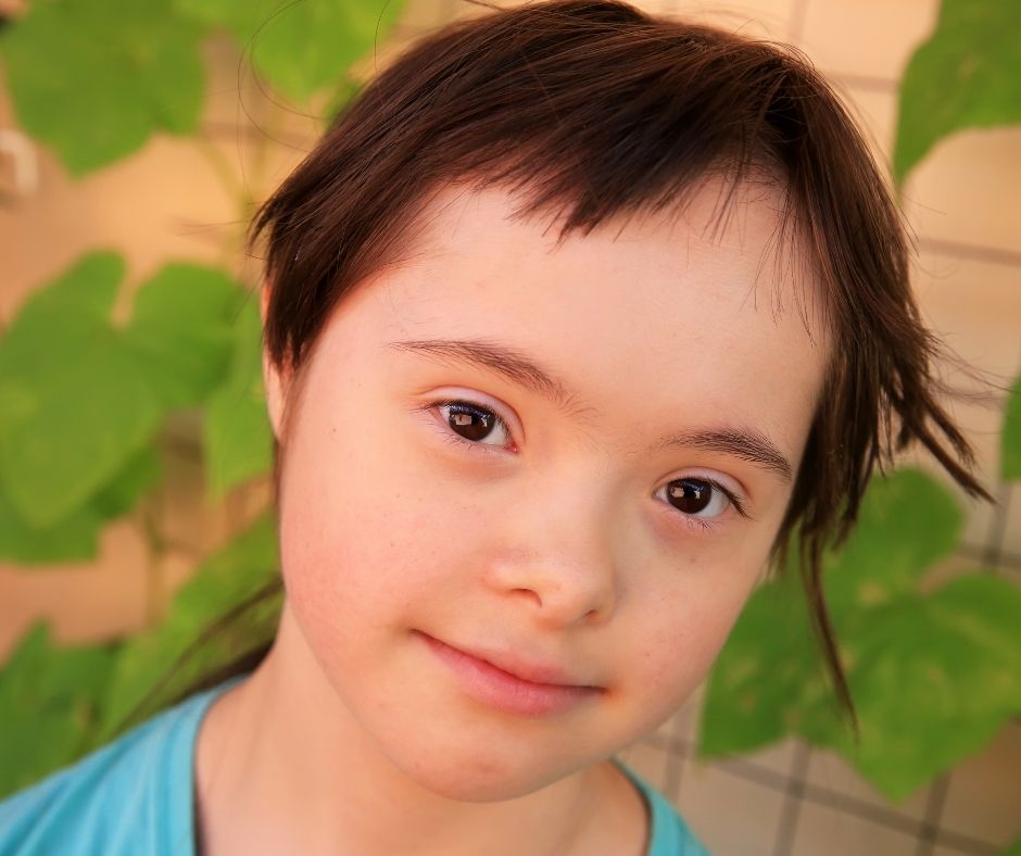 young girl looks at the camera with a half-smile on her lips. her eyes are bright and friendly, she has brown hair and light skin. she has down syndrome