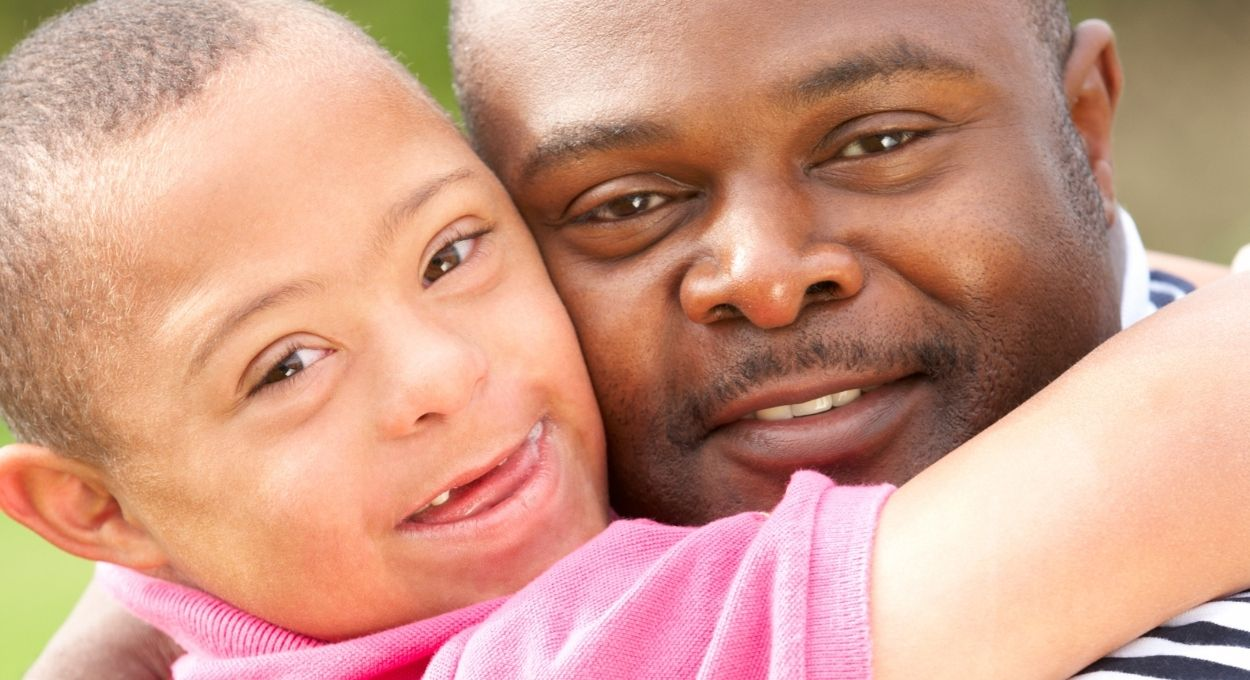 SSI For my Child with a Disability: image of a black man holding a black boy with Down syndrome. they are smiling and their arms are wrapped around one another. Both have short hair, bright eyes. The boy has lighter skin than the man.