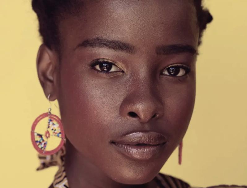 Amanda Gorman: yellow background, a young woman with a piercing gaze. she had dark brown skin and wears orange earrings