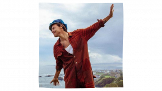 Harry Styles & The Gift of Millennial Neuro-Flexibility: image of a man with red shirt, white undershirt and green beret with his arms outstretched, smiling. He is on a cliff, with his back to the ocean