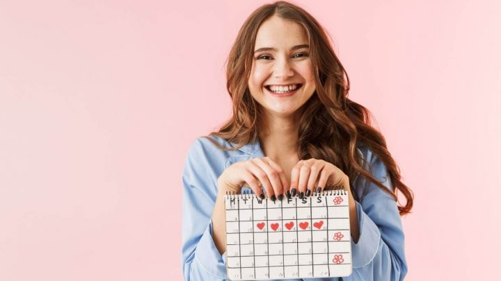 disability awareness calendar and disability awareness months 2021 - image of a pink background and a white girl with long brown hair and a big smile, holding a calendar up with both hands. Her nails are painted black and the calendar has lots of hearts drawn on it