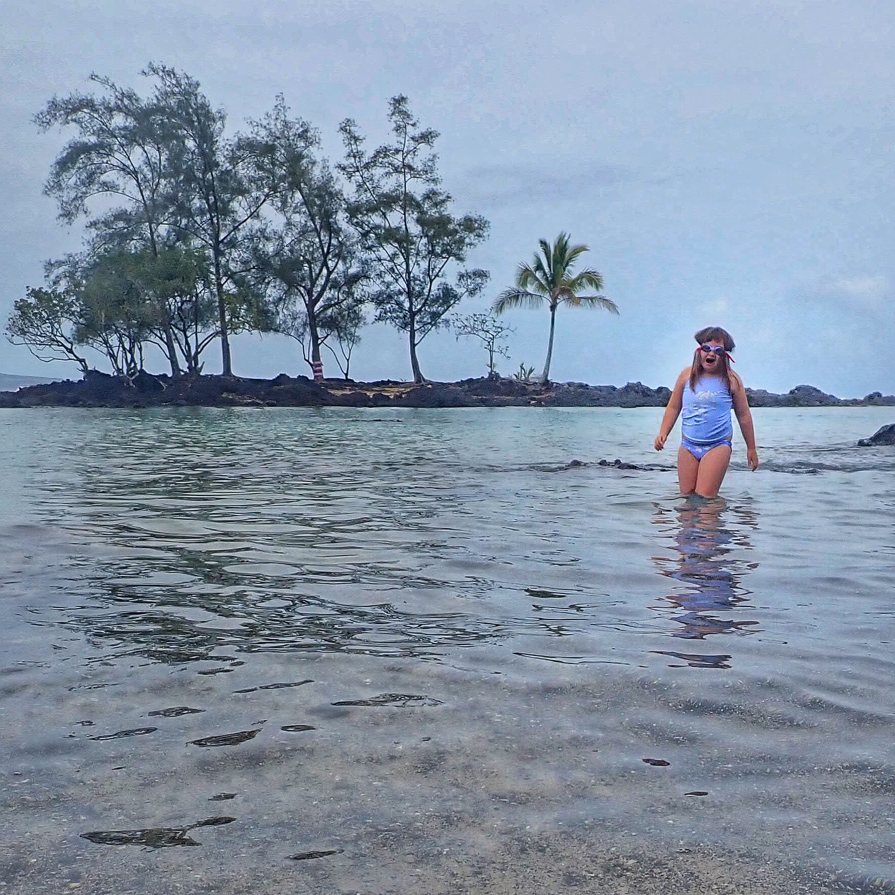 child in water with coconut trees