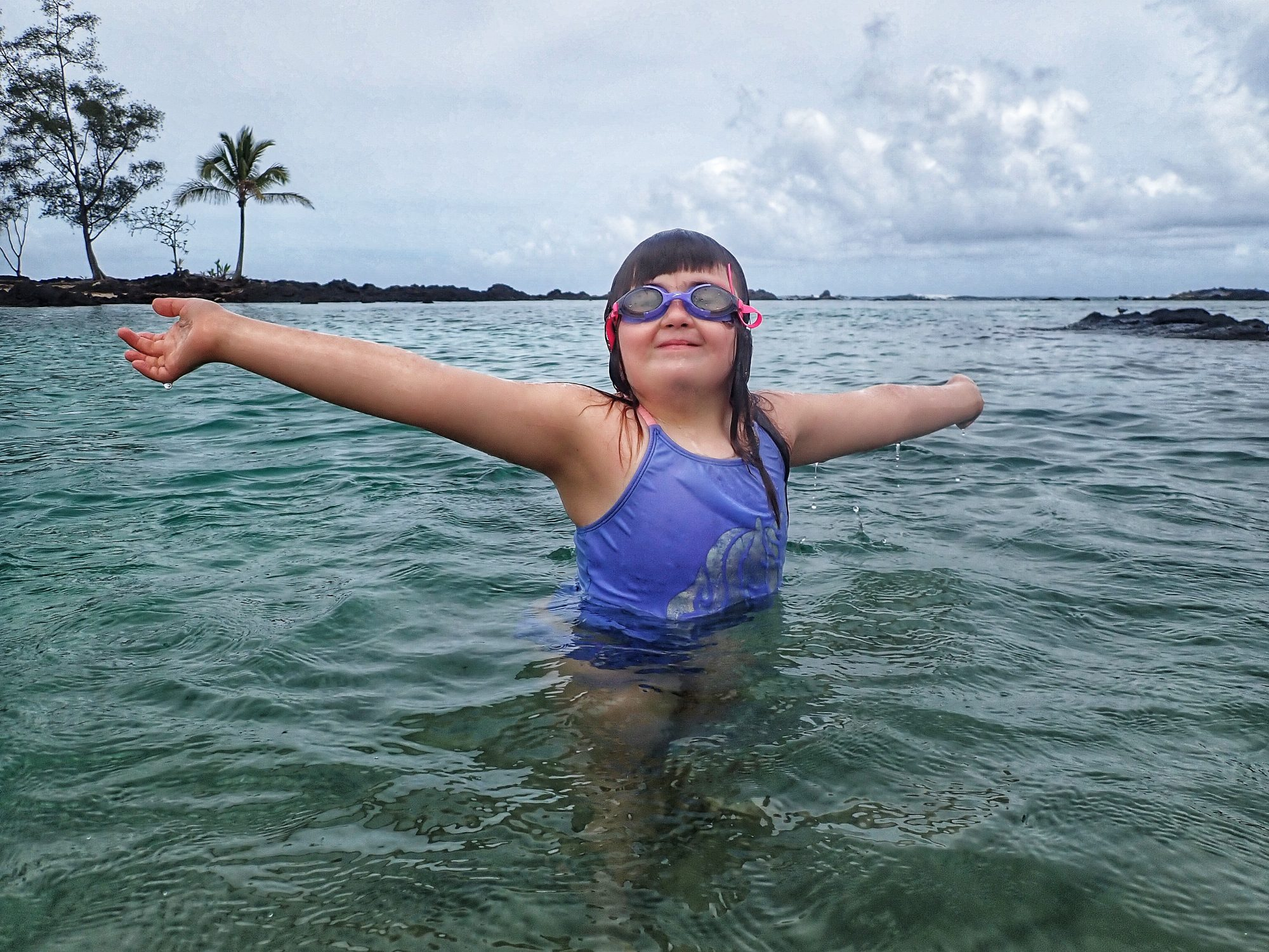 child in water with arms outstretched she is smiling, purple swim suit and goggles on