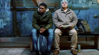 image of two men sitting on a bench, one is black and with green hoodie, hunching over with his hands on a backpack, the other is white and in a tan jacket and hat, looking up with a half smile as he holds paper.