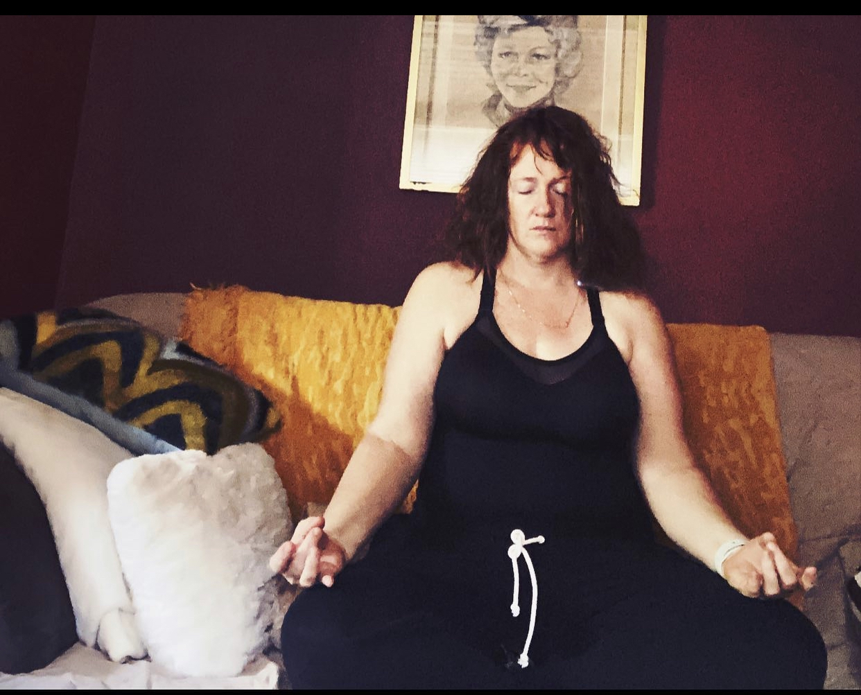 while woman with brown hair sitting cross legged, meditating