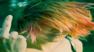 image of a white woman with multicolored hair holding up her middle finger
