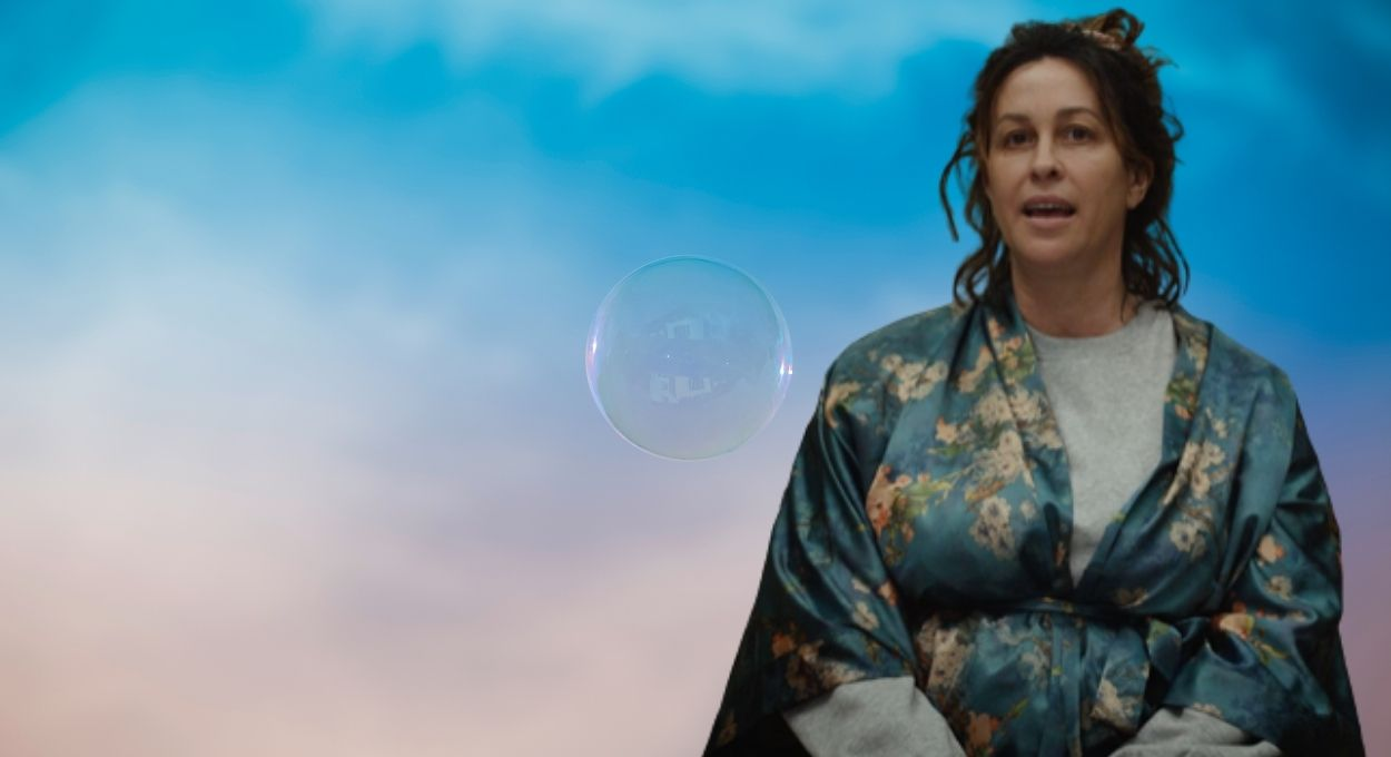 woman in a bathrobe and messy upswept hair has her mouth open, in the background is a soft pastel sky and a bubble