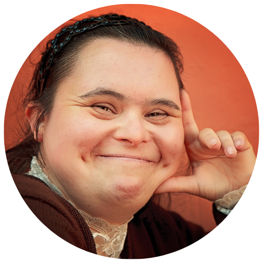 a woman with Down syndrome looks at the camera and smiles wither her left hand propping her head