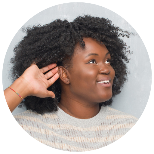 a black woman smiles and has her hand behind her ear