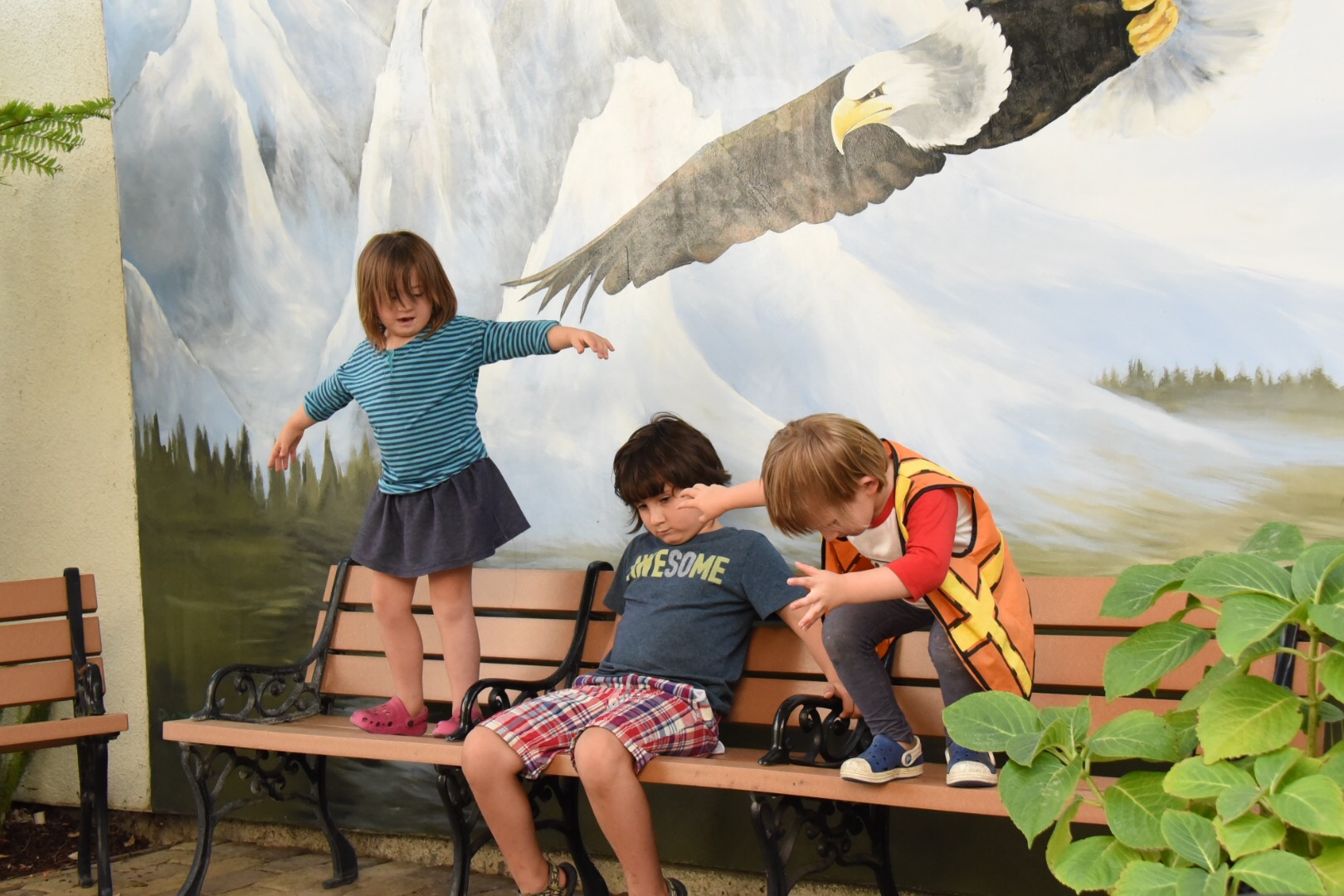 kids on benches under a mural of a bird soaring, they are pretending to fly