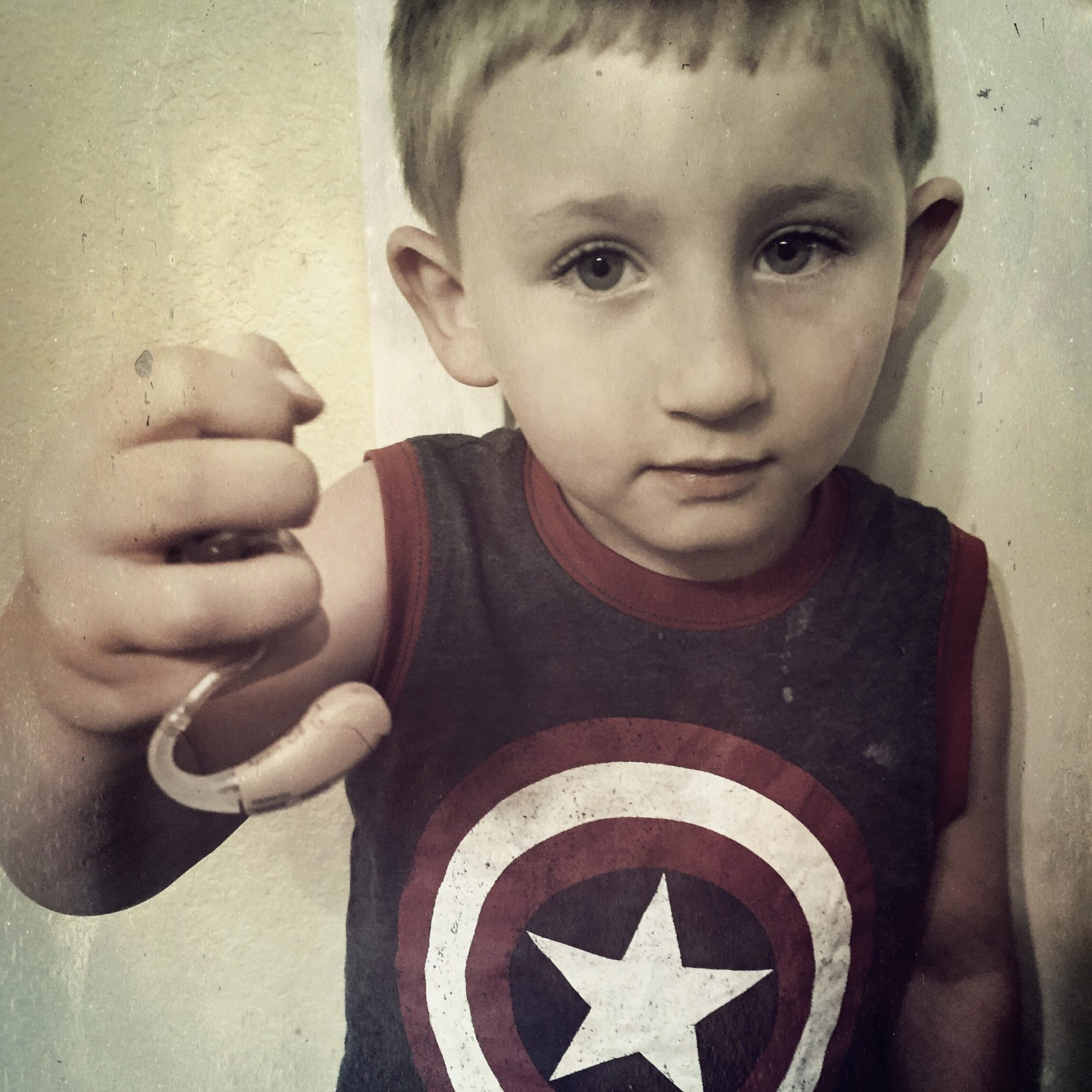 child holding up hearing aids