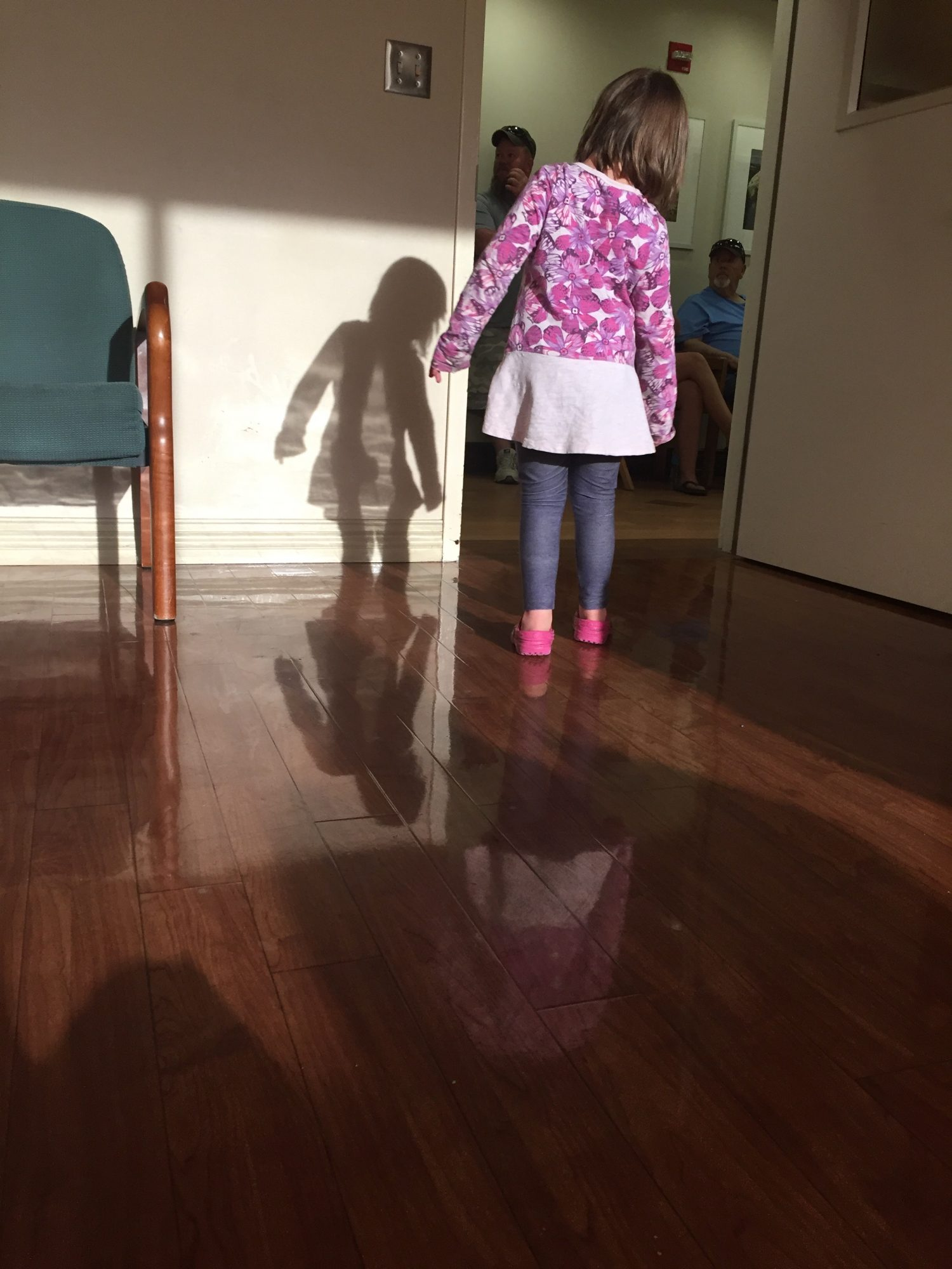 child looking through door and her shadow is on the wall