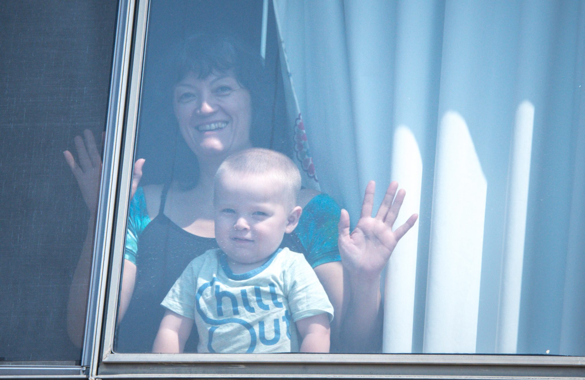 woman smiling in window with baby