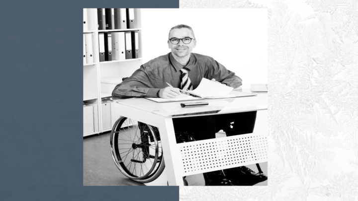 grey and white background, black and white image of a white man with brown hair and glasses sitting at a desk, smiling, he is wearing a shirt and tie and is using a wheelchair