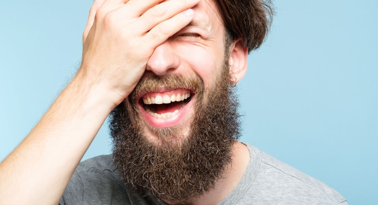 I thought I was stupid - background light blue, white man with brown hair and long brown beard is laughing broadly with his eyes closed; he has his plan over half of his face